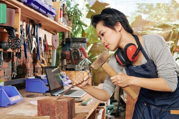 Carpinteira vietnamita usando cinzel e martelo ao trabalhar com madeira dura