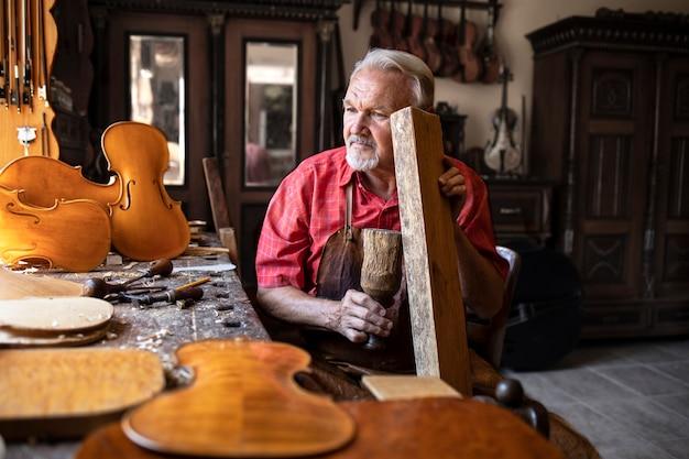 Carpinteiro artesão sênior verificando a qualidade do som do material de madeira em sua oficina de carpinteiro tradicional
