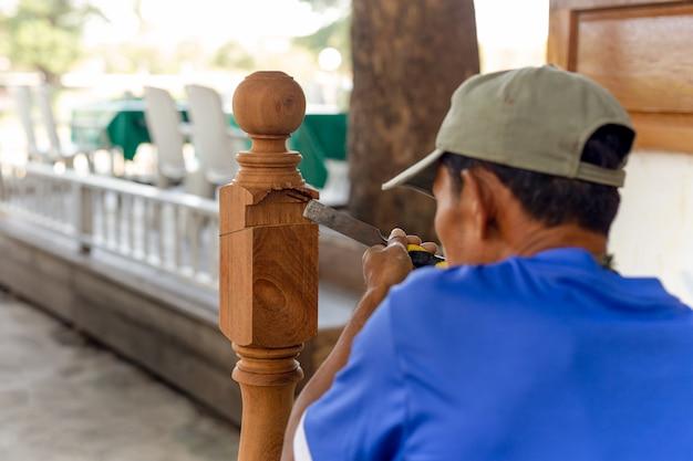 Carpinteiro asiático do homem que trata um de madeira com o formão exterior.