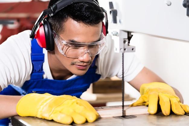 Carpinteiro asiático em serra cortando madeira em oficina