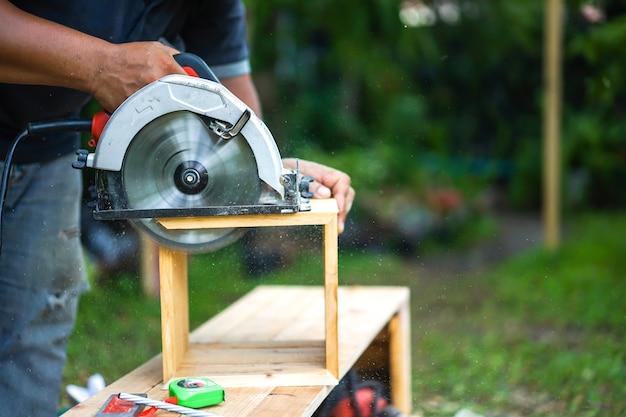 Carpinteiro asiático está a serrar a madeira
