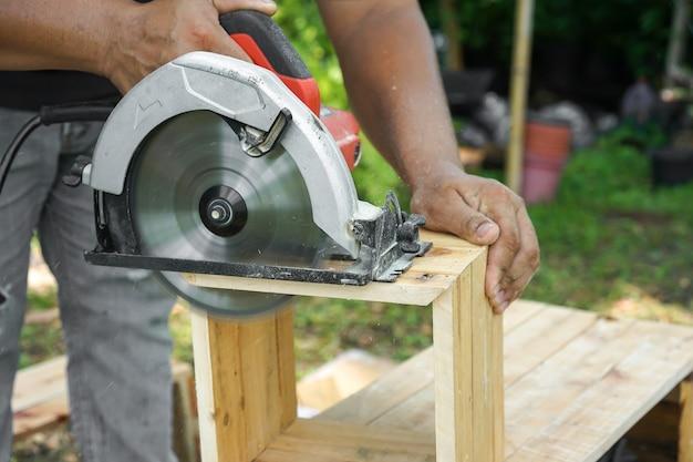 Carpinteiro asiático está serrando a madeira no jardim do quintal de casa.