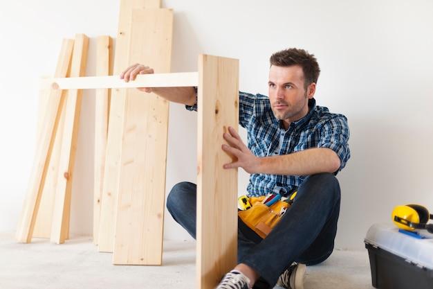 Carpinteiro bonito trabalhando em móveis novos