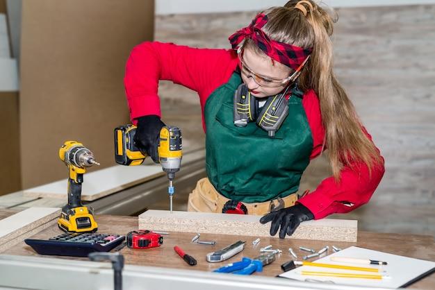 Carpinteiro com chave de fenda construindo móveis em carpintaria