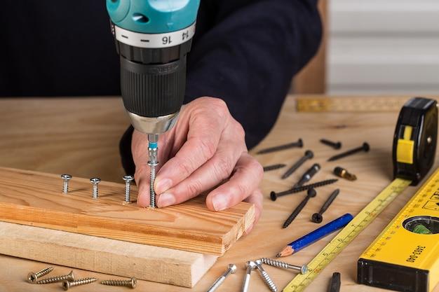 Carpinteiro com chave de fenda elétrica. carpinteiro no trabalho artesanal