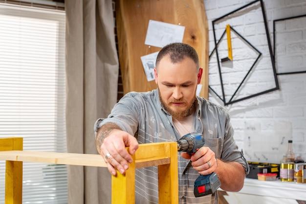 Carpinteiro com furadeira elétrica, prancha de madeira na oficina