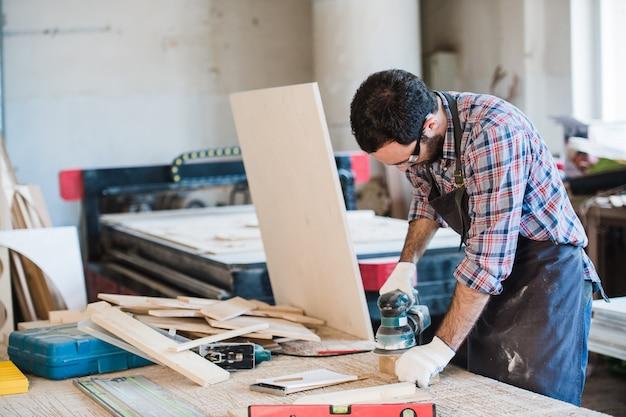 Carpinteiro com moedor de energia em sua oficina