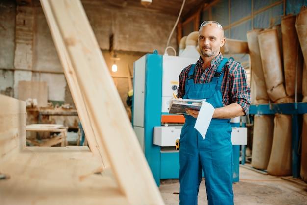 Carpinteiro com notebook, processamento de madeira, fábrica