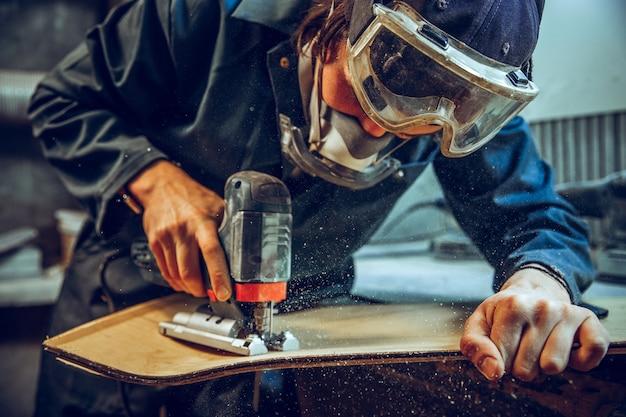Carpinteiro com serra circular para cortar tábuas de madeira.