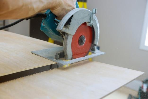 Carpinteiro corta madeira compensada em uma serra circular elétrica