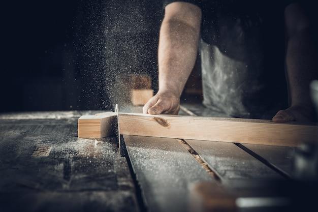 Carpinteiro corta prancha de madeira na serra circular