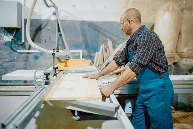 Carpinteiro corta tábua de madeira em máquina de serra circular, marcenaria, indústria madeireira, carpintaria.