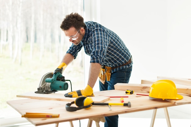Carpinteiro cortando tábua com serra circular