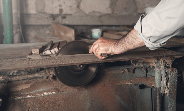 Carpinteiro cortando um pedaço de madeira com uma máquina de carpintaria.