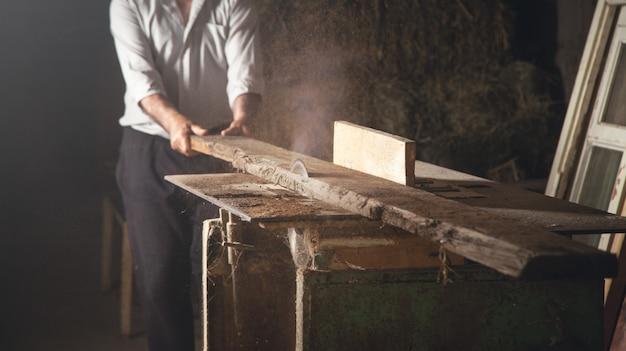 Carpinteiro cortando uma prancha de madeira com uma máquina de carpintaria.