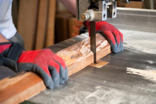 Carpinteiro cortar madeira em uma serra de fita