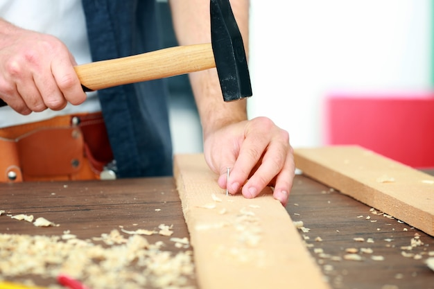 Carpinteiro cravando o prego na placa de madeira na oficina, closeup