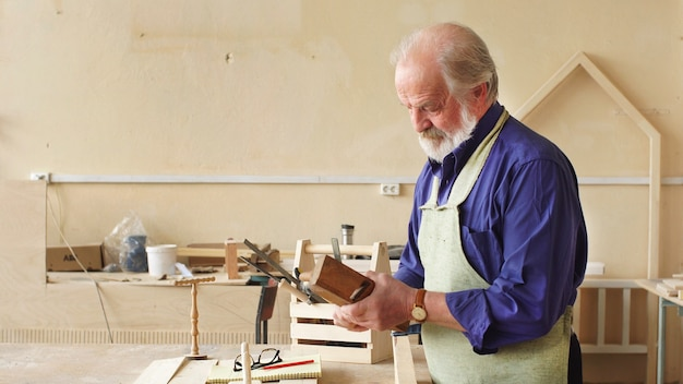 Carpinteiro de cabelos grisalhos trabalha em sua oficina. o conceito de madeira