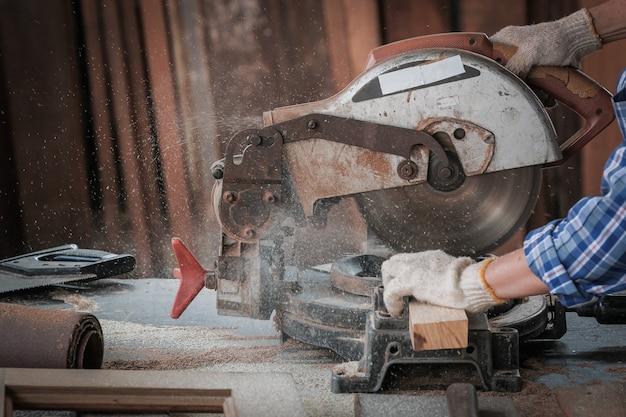 Carpinteiro de homem forte usando serra de mesa conceito de trabalho industrial