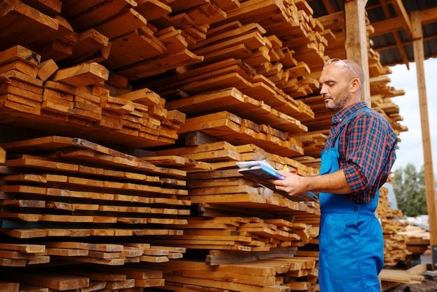 Carpinteiro em placas de verificação uniforme em serraria, indústria madeireira, carpintaria. processamento de madeira na fábrica, corte florestal em madeireira, armazém ao ar livre