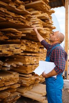 Carpinteiro em tábuas de xadrez uniforme em serraria