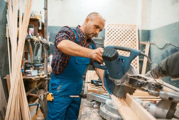 Carpinteiro em uniforme trabalha em serra circular, marcenaria, madeireira, carpintaria. processamento de madeira em fábrica de móveis, produção de produtos de materiais naturais