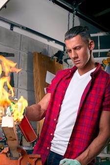 Carpinteiro especialista que queima uma perna de madeira com um queimador de gás profissional. chamas e fumaça, fogo e madeira. retrato de armários