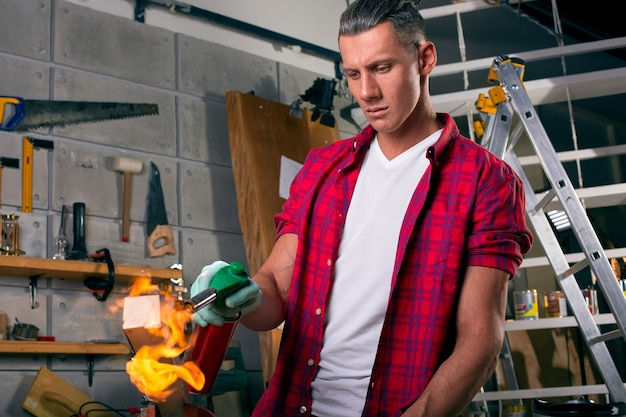 Carpinteiro especialista queimando uma perna de madeira com um queimador de gás profissional
