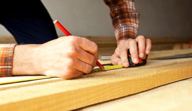 Carpinteiro está medindo o comprimento da placa de madeira com fita métrica