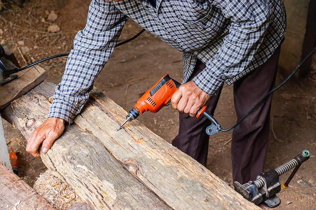 Carpinteiro está trabalhando para perfurar madeira