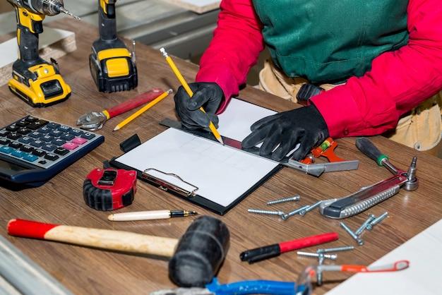 Carpinteiro fazendo esquise para futuros móveis