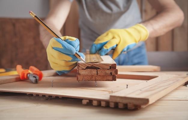 Carpinteiro fazendo marcas na prancha de madeira com um lápis.