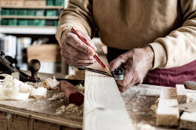 Carpinteiro, fazendo medições com um lápis e uma régua de metal na prancha de madeira