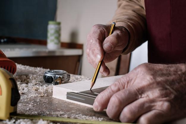 Carpinteiro fazendo medições em uma mesa com um lápis e um quadrado de metal