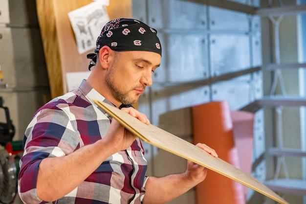 Carpinteiro fazendo seu trabalho na oficina de carpintaria. homem em uma oficina de carpintaria mede e corta laminado