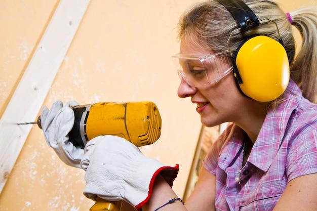 Carpinteiro feminino no trabalho usando a máquina de perfuração de mão