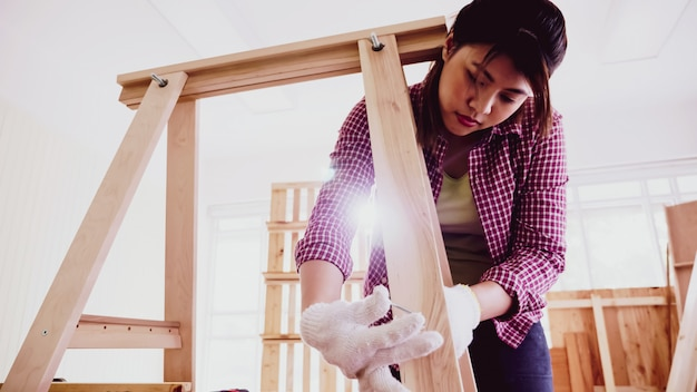 Carpinteiro feminino transando com pedaços de tábuas juntos no local.