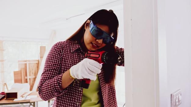 Carpinteiro feminino usando broca para parafusar a parede no local.