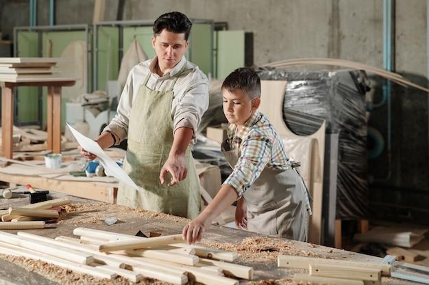 Carpinteiro habilidoso usando avental apontando para detalhes de madeira enquanto ensina o filho a fazer móveis na oficina