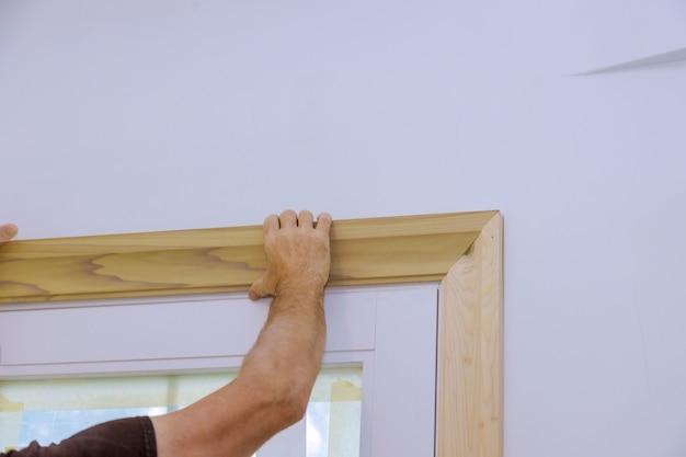 Carpinteiro instalando nas molduras das portas, pregando o acabamento da moldura
