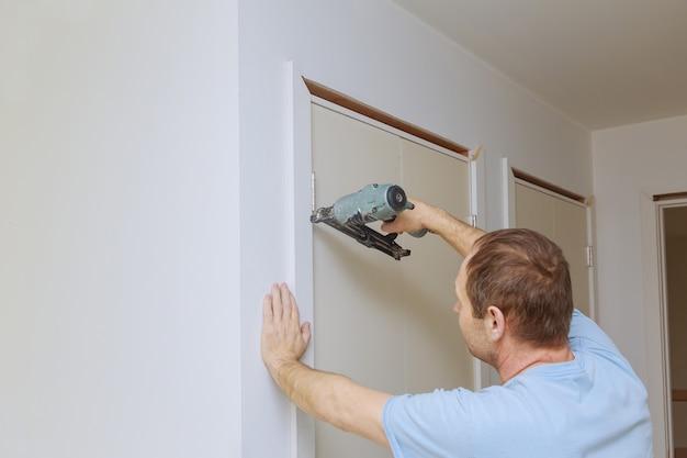 Carpinteiro instalando pregar a guarnição da moldura nas molduras das portas