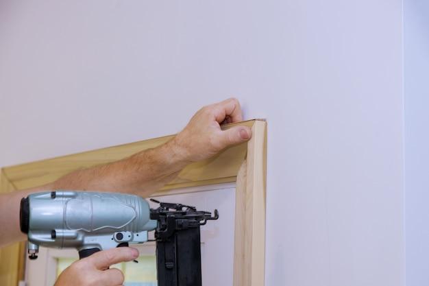 Carpinteiro instalando pregar o acabamento da moldura nas molduras das portas