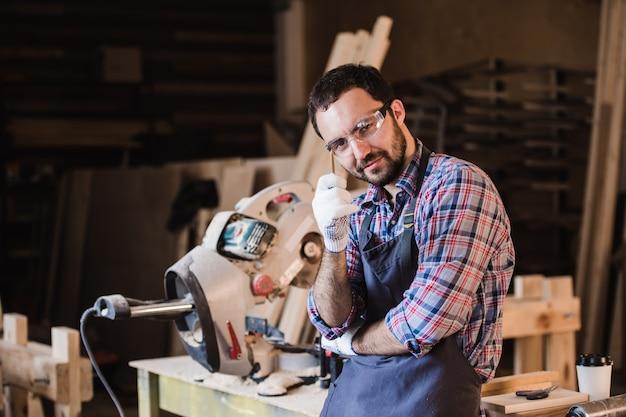 Carpinteiro jovem bonito trabalhador manual na oficina, sorrindo