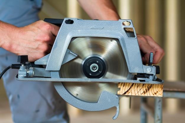 Carpinteiro mãos usando uma serra elétrica para cortar tábua de madeira