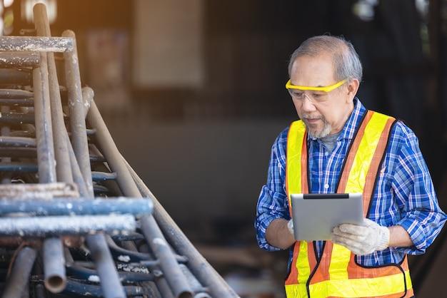 Carpinteiro masculino em uma oficina de construção, usando um tablet digital