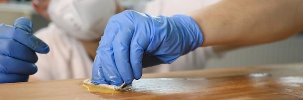 Carpinteiro masculino esfrega a mistura na superfície de madeira.