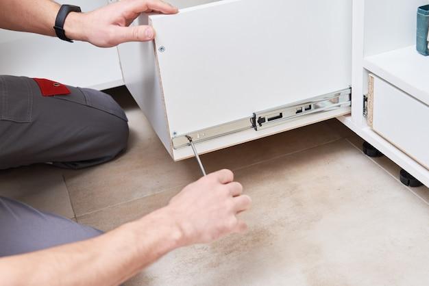 Carpinteiro masculino instala prateleira no armário da cozinha
