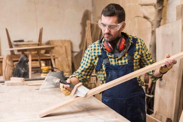 Carpinteiro masculino, limpeza da prancha com escova