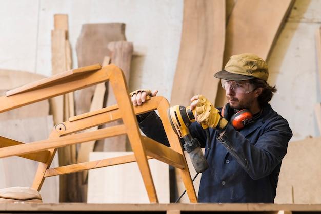 Carpinteiro masculino lixar uma madeira com lixadeira orbital em uma oficina