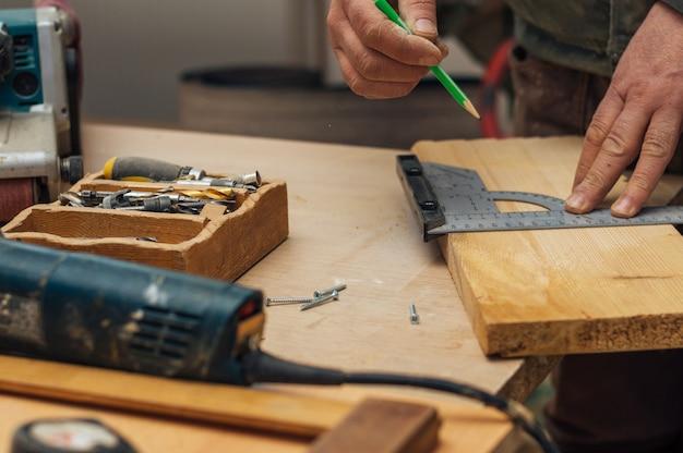 Carpinteiro masculino mãos marca de desenho no revestimento de madeira com régua e lápis.
